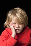 Boy with toothache. Small boy holding his cheek due to severe toothache Stock Photography