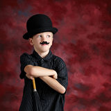 Boy with top hat mustache. Studio portrait of a boy wearing a black top hat, fake mustache, leaning on an umbrella.  Reddish background Royalty Free Stock Images