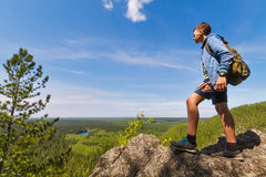 Boy at the top of a hill with blue sky. Teenager on the top of a cliff looking at Baikal lake Stock Photo