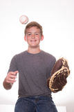 Boy tossing baseball into glove. Boy smiling while tossing a baseball into a glove Royalty Free Stock Photos