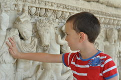 A boy touches historical monument. A schoolboy look a historical monument and touches it stock photos