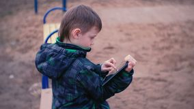 Boy touches a screen of tablet sitting in the Park on a bench. Side view. Boy touches a screen of tablet sitting in the Park on a bench stock video