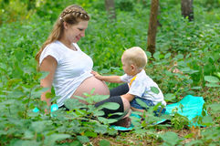 The boy touches a stomach of pregnant mother. Pregnant mother and son on the fringe of the forest Stock Photos
