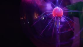 Boy touches to plasma globe. Boy touches to the plasma globe in scientific museum. Tesla globe with electric impulses inside. The museum of popular science and