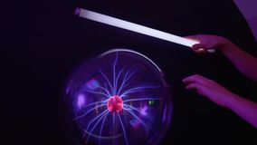 Boy touches to plasma globe with lamp. Boy touches to the plasma globe in scientific museum with lamp. Tesla globe with electric impulses inside. The museum of stock video footage