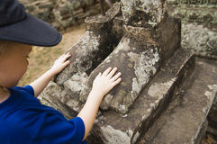 Boy Touching Feet Of Ancient Statue Stock Photos