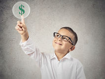 Boy touching green dollar sign. Closeup portrait happy, smiling child touching green dollar sign button on a touchscreen display, isolated  grey wall background Stock Photos