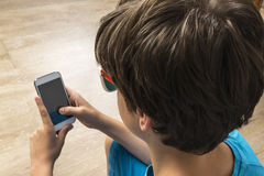 Boy touching a smartphone Royalty Free Stock Photos