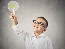 Boy touching yellow euro currency sign. Closeup portrait happy, smiling child touching yellow euro currency sign button on touchscreen display isolated grey wall royalty free stock photos