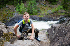 Boy tourist standing near the mountain waterfall. Boy tourist with a backpack standing near the mountain waterfall Royalty Free Stock Image