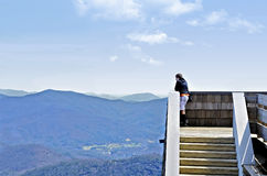 Boy on Tower in Mountains. A young boy on an observation tower looking out over the mountains at Brasstown Bald in Georgia stock photo
