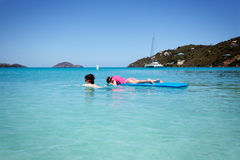 Boy tows girl on raft Stock Image