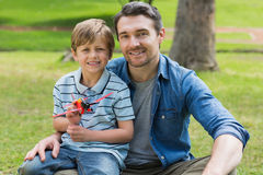Boy with toy aeroplane sitting on father's lap at park Stock Images