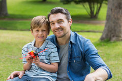 Boy with toy aeroplane sitting on father's lap at park Stock Photos