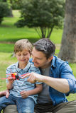 Boy with toy aeroplane sitting on father's lap at park Stock Photography