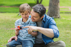 Boy with toy aeroplane sitting on father's lap at park Royalty Free Stock Photography