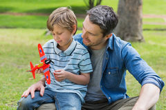 Boy with toy aeroplane sitting on father's lap Stock Photos