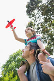 Boy with toy aeroplane sitting on father's shoulders Royalty Free Stock Photography