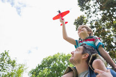 Boy with toy aeroplane sitting on father's shoulders. Low angle view of a boy with toy aeroplane sitting on father's shoulders at the park Stock Photo