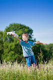 Boy with toy airplane. Happy kid playing with toy airplane against blue summer sky background. Laughing boy with plane in green field. Best childhood concept stock photography