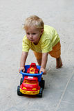 Boy and toy car. A little boy playing outdoors with his plastic toy car royalty free stock photography