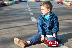 Boy with a toy car. Four year old boy sits on the road with toy car in the hands. Season - spring Royalty Free Stock Image