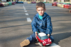 Boy with a toy car. Four year old boy sits on the road with toy car in the hands. Season - spring Royalty Free Stock Images