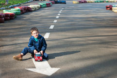 Boy with a toy car. Four year old boy sits on the road with toy car in the hands. Season - spring Royalty Free Stock Photo