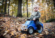 Boy with toy car. Small blond boy driving blue toy car over carpet of leaves,  forest background Stock Photos