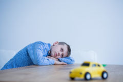 Boy and toy car on a table. Thoughtful little boy and toy car on a table Royalty Free Stock Image