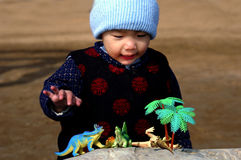 Boy and toy dinosaurs. Boy watching the fight of the toy dinosaurs royalty free stock images