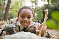 Boy with toy dinosaurs Stock Photos