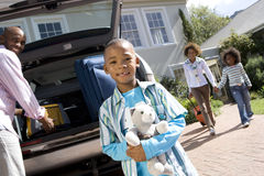 Boy (6-8) with toy by father loading back of car, portrait (tilt) stock photography