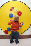 Boy and Toy Gears. A little boy looks carefully at some colorful gears on a yellow circle board Royalty Free Stock Images