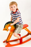 Boy on toy horse Stock Image
