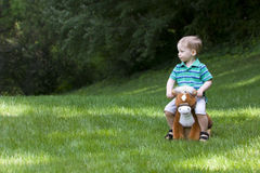 Boy on toy horse Stock Photo
