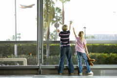 Boy (8-10), with toy plane, and girl (7-9), with soft toy, looking through large window in airport departure lounge, watching aero Stock Photo