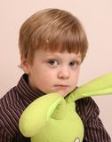 Boy With Toy Rabbit. Young boy wearing striped shirt and playing with toy rabbit Royalty Free Stock Photo