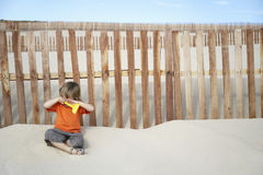 Boy With Toy Rake Sitting Against Wooden Fence On Beach Royalty Free Stock Image