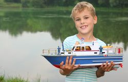 Boy with toy ship in hands ashore. Summer royalty free stock images