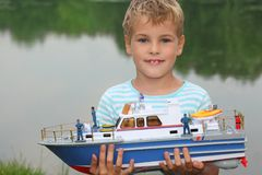 Boy with toy ship in hands ashore. Summer royalty free stock photography