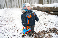 Boy with a toy in a snowy forest Royalty Free Stock Photography