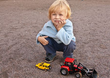 Boy with toys. Boy having rest on playground, sitting and thinking, playing with toys Stock Photos