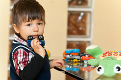 Boy with toys. Portrait of a thoughtful boy standing at a table with toys Stock Photos