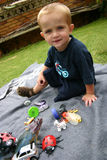 Boy with toys. Boy playing on blanket with toys Stock Images