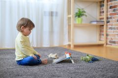 Boy and toys with tablet computer. On carpet royalty free stock images