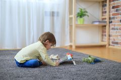 Boy and toys with tablet computer. On carpet stock images