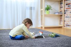Boy and toys with tablet computer. On carpet stock photos