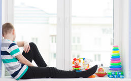 Boy with toys on a windowsill Stock Images