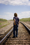 Boy on Tracks. Boy Standing on Railroad tracks facing away from the camera Royalty Free Stock Photo